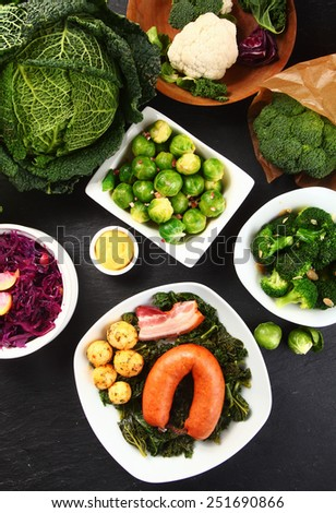 Close up Aerial Shot of Fresh Ingredients with Brussels Sprouts, Cabbage, Cauliflower, Potatoes, Broccoli and Meats on Top of Wooden Table. - stock photo