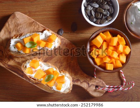 Close up Aerial Shot of Healthy Creamed Bread with Filling on Top of Wooden Cutting Board with Bowl of Carrot Slices and Pumpkin Seeds on the Side. - stock photo