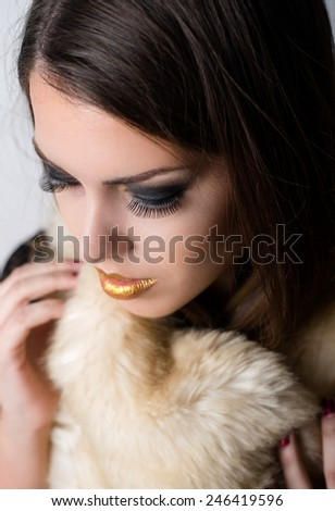 Close up Aerial View of Pretty Young Woman Wearing Dark Eye Shadows and Gold Lips Make - up with Winter Fur Scarf. - stock photo