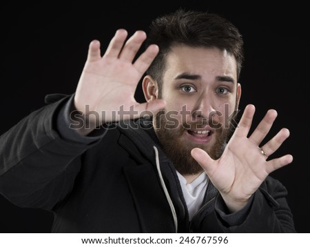 Close up Afraid Goatee Young Man in Dark Jacket, Raising his Hands Up While Looking at the Camera. Isolated on Black - stock photo
