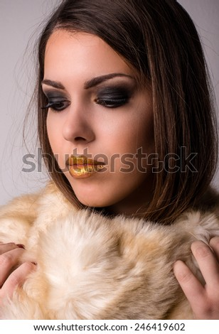 Close up Alluring Young Woman, with Gold Lips, Wearing Winter Furry Scarf on Light Brown Background. - stock photo
