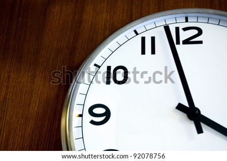 close up almost twelve on wall clock - stock photo