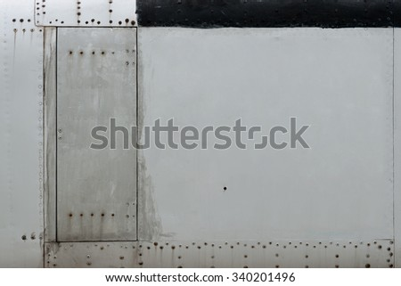 Close up aluminum fuselage and rivets on old airplane. - stock photo