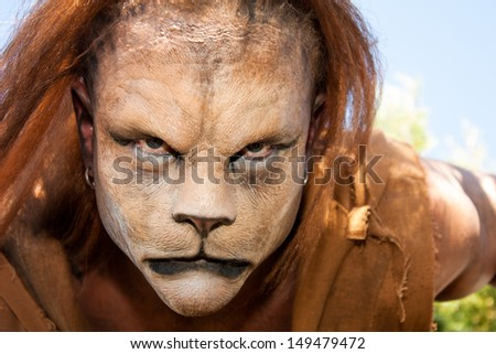 Close -up and meancing face of a Lion man looking into the camera.  Fantastic special FX make up of Rayce Bird. - stock photo