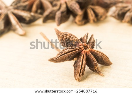 Close up and selective focus on one piece of Star Anise at the foreground on wooden surface - stock photo