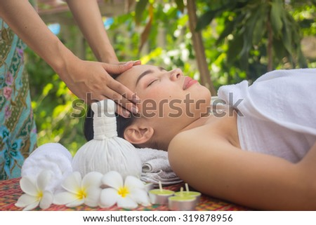 close up and selective focused on young beautiful asian woman are massaging:Thai woman in spa treatment :woman relaxing wellness concept.natural outdoors spa treatment concept :soft focused concept.