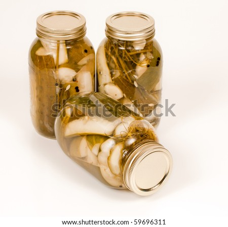 Close up angled studio view of three jars of homemade pickles. - stock photo