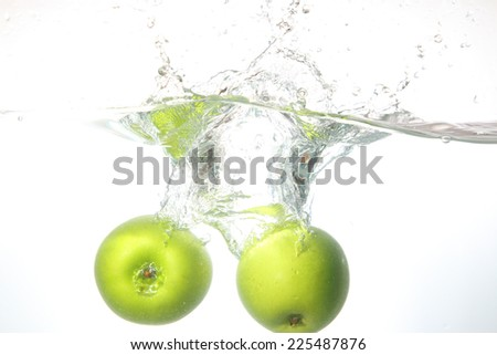 Close up apple fell into the water, white background.