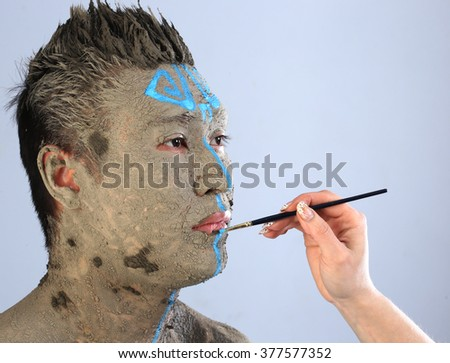 close-up apply artist brush pattern on the skin of a man in the clay