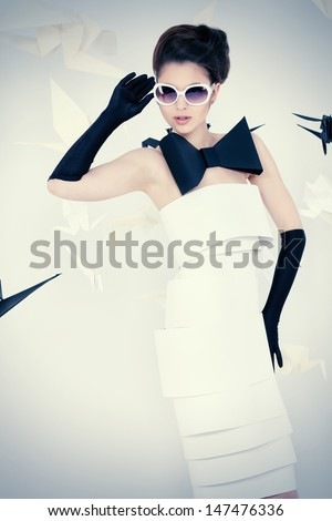 Close-up art fashion photo of a gorgeous woman in paper dress. Black and white.