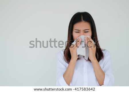 close up asian woman got a cold:young girl holding tissue in hand for reaction sneezing :healthcare concept.runny nose:sore or scratchy throat:risk of living:severe allergies:avoid and preventive - stock photo