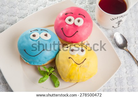 Close up Assorted funny faces colourful donuts on on white plate a on kitchen table - stock photo
