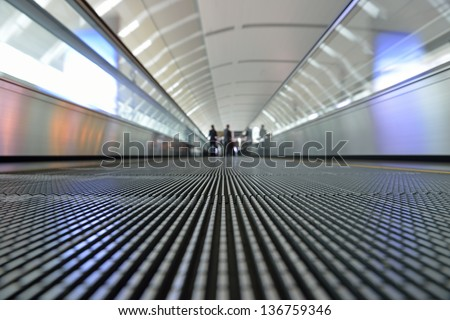Close-up at airport conveyor belt with blurry people in motion - stock photo