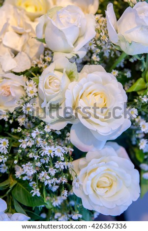 Close up at white rose with decorate flower in bouquet for Wedding Day,  White roses flowers, elegant bouquet tied. Image of  Rose Wedding bouquet in romantic worm light  - stock photo