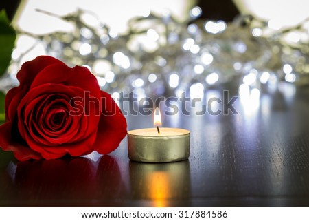 Close up Attractive Fresh Red Rose Flower and Small Lighted Candle on Wooden Table - stock photo