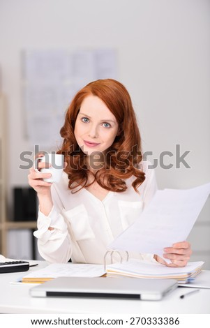 Close up Attractive Office Woman with Brown Hair Holding Report Papers and a Cup of Coffee While Looking at Camera with a Smile. - stock photo