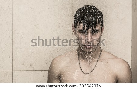 Close up Attractive Young Bare Muscular Young Man Taking Shower, Looking at Camera - stock photo
