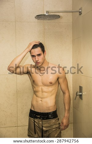 Close up Attractive Young Bare Muscular Young Man Taking Shower with One Hand on his Head, Looking at Camera - stock photo