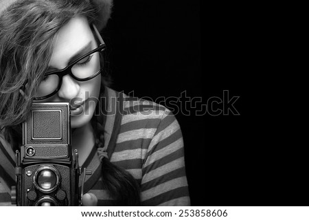 Close up Attractive Young Woman in Trendy Outfit Capturing Photo Using Vintage Camera. Black and White Portrait Isolated on Black Background with Copy Space for Text. - stock photo