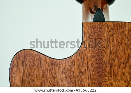 close up back guitar wood curve on soft green background, brown and gold wooden grain, curve part of music instrument - stock photo