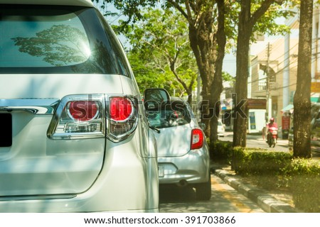 Close up back of 2 cars parking on the road and under tree - stock photo