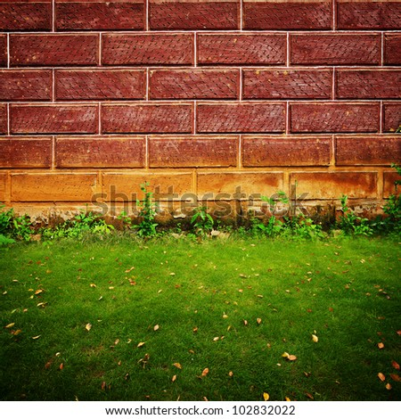 close up background make with brick and green grass field - stock photo