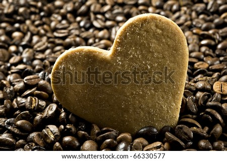 Close up background of a sugar coated heart shaped cookie in  coffee beans   very shallow depth of field and intentional low light - stock photo