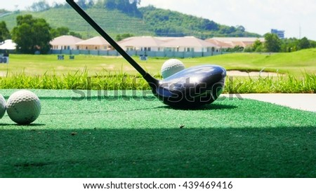 Close up ball on tee retired golfer taking swing hitting golf ball off tee on golf course - stock photo