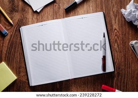 Close up Ballpoint Pen on Open Blank Notes, with Other Supplies on Sides, Placed on Wooden Table. Emphasizing Copy Space for Texts at the Center. - stock photo
