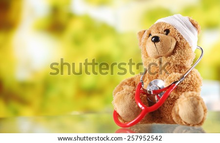 Close up Bandaged Plush Teddy Bear with Stethoscope Device on Top of a Glass Table, Emphasizing Copy Space. - stock photo