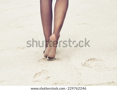 Close up Bare Dark Woman Feet While Walking at White Beach Sand on a Sunny Day. - stock photo