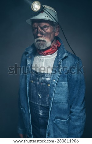 Close up Bearded Senior Male Mine Worker, Wearing Denim Jacket and Helmet with Lamp, Looking Straight at the Camera in a Serious Facial Expression.