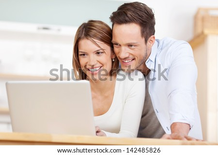 Close up beautiful couple working on laptop at home - stock photo