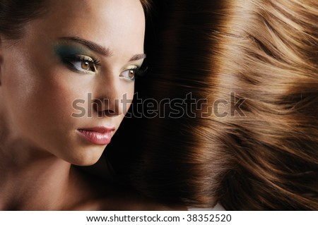 Close-up beautiful female face with luxuriant long hair as a background - stock photo