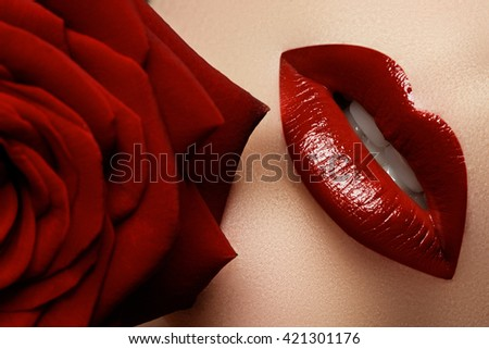 Close-up beautiful female lips with bright red makeup. Perfect clean skin, sexy lip make-up. Beautiful spa portrait with tender red rose flower. Spa and cosmetics - stock photo