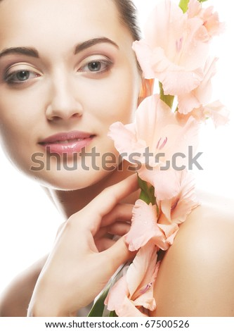 Close-up beautiful fresh face with gladiolus flowers in her hands