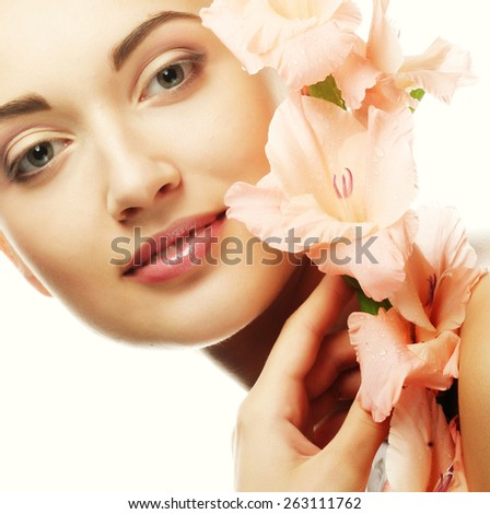 Close-up beautiful fresh face with pink gladiolus flowers in her hands - stock photo