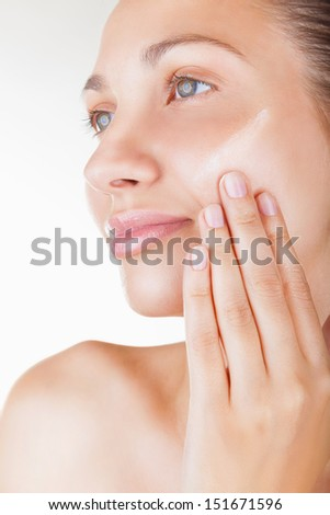 Close-up beautiful woman applying moisturizer cosmetic cream on face on light background - stock photo