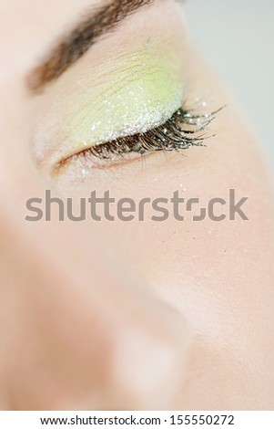 Close up beauty detail of a young and attractive woman eye wearing acidic party green glitter sparkling eyeshadow and mascara with her eyes closed, interior. - stock photo