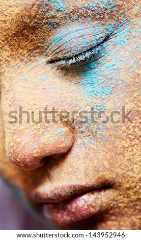 Close up beauty part portrait of a young girl face with voluptuous lips wearing golden yellow and blue and make up powder pigment covering her face, detail texture view.