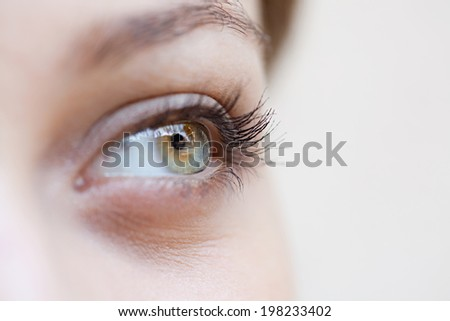 Close up beauty portrait detail section view of an attractive young woman eye looking up to the side, being thoughtful and calm, wearing cosmetics. Healthy skin, sight and beauty care, wellness. - stock photo