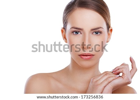 Close-up, beauty portrait of a beautiful, young woman gently holding hands together by the side.retouched with special care and attention; Small amount of grain added for best final impression. - stock photo