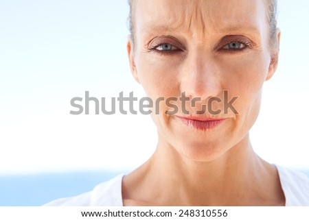 Close up beauty portrait of a senior mature healthy woman being worried and thoughtful, stressed and emotional. Mature and aging face with an unhappy and strong expression, outdoors. - stock photo