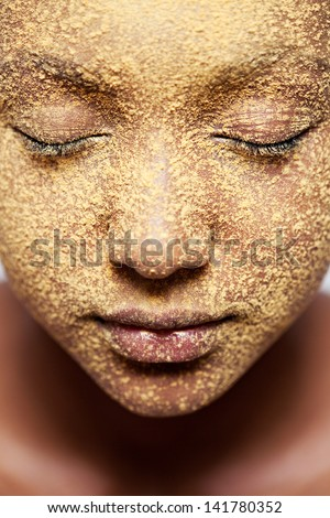 Close up beauty portrait of a young african american black girl face with yellow cosmetic powder covering her face, with her eyes closed.
