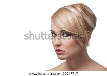 close up beauty portrait of a young and cute blond girl with hair style over white. Her face is turned three quarters, she looks in to the lens with actractive eyes.