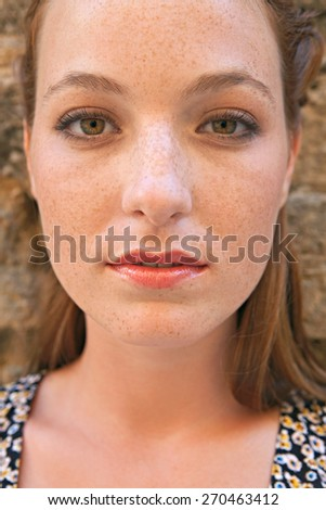 Close up beauty portrait of an attractive young tourist woman visiting a city street with textured stone walls on holiday. Travel and lifestyle vacation living. Thoughtful woman portrait, outdoors. - stock photo