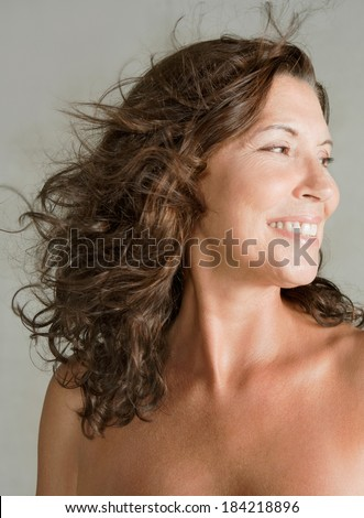 Close up beauty portrait of an elegant mature woman with bare shoulders, smiling against a plain gray wall background while her hair is flying and floating in the breeze. Beauty lifestyle.