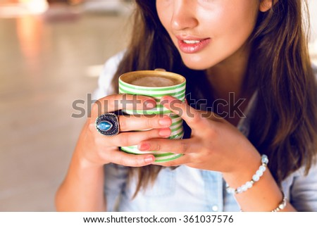 Close up beauty portrait of beauty brunette woman, nice natural glowing make up, holding cup with her morning coffee, trendy jewelry, cafe, hot beverage, enjoy. - stock photo