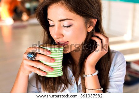 Close up beauty portrait of beauty brunette woman, nice natural glowing make up, holding cup with her morning coffee, trendy jewelry, cafe, hot beverage, enjoy. close her eyes. - stock photo