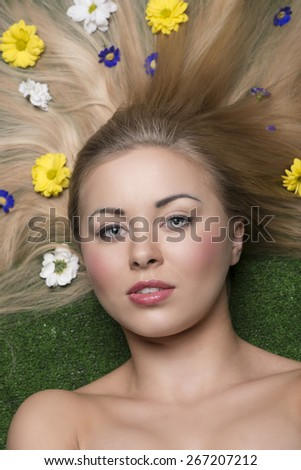 close-up beauty portrait of blonde woman with perfect skin and long smooth hair lying on garden with some colourful flowers in the hair  - stock photo